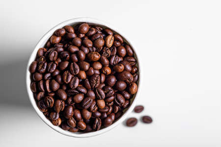 roasted coffee beans in white paper Cup on white background, top view