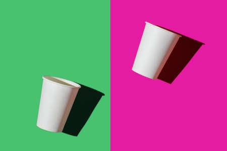two white paper biodegradable cups on colored backgrounds, top view, mock up, copy space