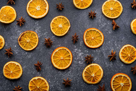 dried orange slices with star anise on gray background, kitchen background, top view, citrus composition concept