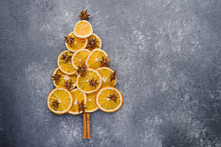 Christmas tree made of dried orange slices, decorated with star anise and cinnamon sticks on gray background, copy space, top view