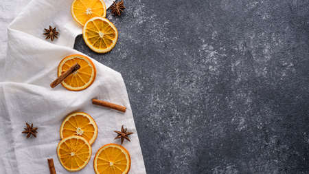festive new year kitchen background, dried orange slices, cinnamon sticks, star anise on white towel on gray table, copy space, top view Archivio Fotografico