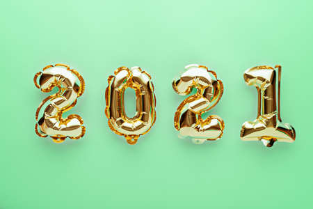 gold foil balloons numbers 2021 on green background, new year's composition, concept