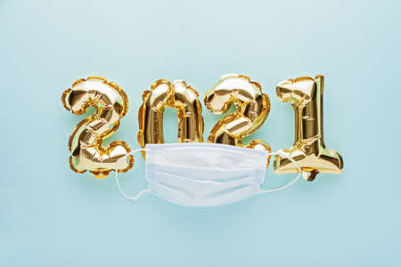 gold foil balloons numbers 2021 with medical mask on blue background, Christmas, new year's day during pandemic coronavirus, COVID Holiday, Pandemic Holiday concept