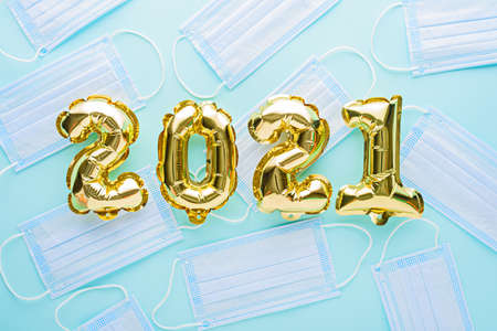 gold foil balloons numbers 2021 with medical mask on blue background, Christmas, new year's day during pandemic coronavirus, COVID Holiday, Pandemic Holiday concept, top view, flat lay Archivio Fotografico