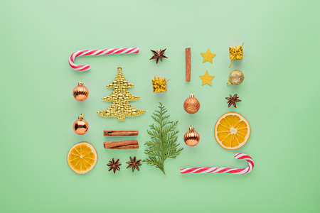 Christmas composition. Sweets, toys, balloons, gold fir on green background, top view, minimal flat lay