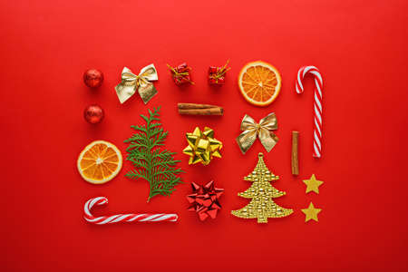 Christmas composition. Sweets, toys, balloons, gold fir on red background, top view, minimal flat lay, new year background Archivio Fotografico