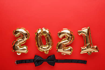 gold foil balloons numbers 2021 with black bow tie on red background, new year's composition, festive dinner concept, Christmas celebration, top view, copy space Archivio Fotografico