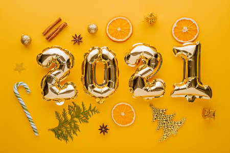 Christmas composition. Gold foil balloons numbers 2021 on yellow background with holiday decorations, objects, top view, festive flat lay