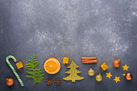 Christmas composition on gray background, candy, Christmas toys, balloons, stars, dried orange, copy space, top view, menu, festive kitchen background