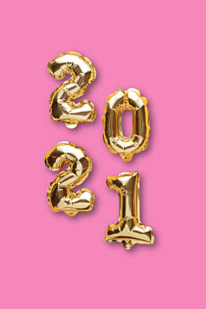 vertical gold foil balloons numbers 2021 on pink background, christmas composition, top view, flat lay Archivio Fotografico