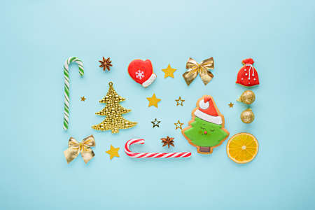 Christmas composition. Sweets, handmade cookies, toys, balloons, gold fir, stars on blue background, top view, minimal flat lay