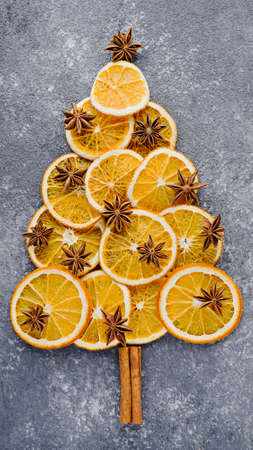 Christmas tree made of dried orange slices, decorated with star anise and cinnamon sticks on gray background, vertical, top view, concept