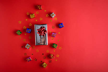 gift boxes with sequins on red background, copy space, top view Archivio Fotografico