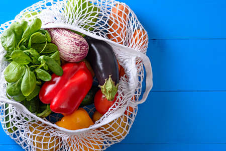 vegetable basket, pepper, eggplant, spinach in white eco bag on blue background, food delivery, copy space, top view
