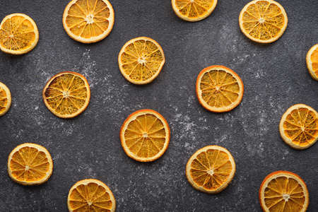 dried orange slices on gray background, kitchen background, top view, citrus composition