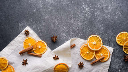dried orange slices, cinnamon sticks, star anise on white towel on gray table, copy space, top view, festive new year kitchen background, Christmas menu Archivio Fotografico