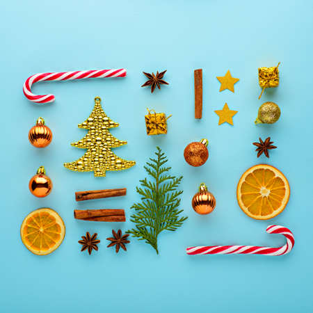 Christmas composition. Candy, decorations, toys on blue background, top view, flat lay festive background