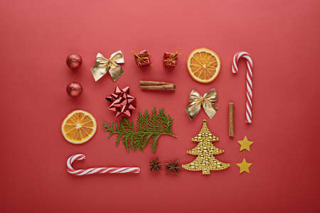 Christmas composition. Candy, decorations, toys on red background, top view, flat lay festive new year background Archivio Fotografico