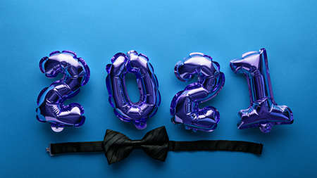 foil balloons numbers 2021 with black bow tie, bowtie on blue background, christmas composition, concept, top view, invitation to festive Christmas dinner Archivio Fotografico
