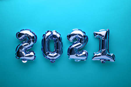 foil balloons numbers 2021 on blue background, christmas composition, concept, top view