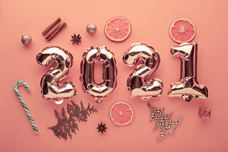 Christmas composition. Gold foil balloons numbers 2021 on toned background with holiday decorations, top view, festive flat lay