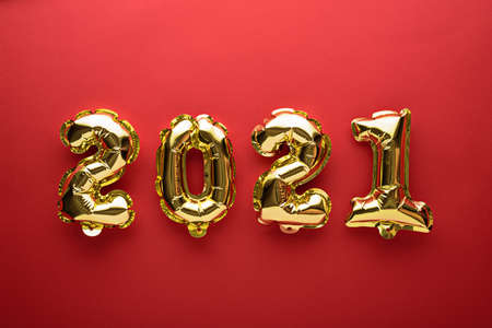 gold foil balloons numbers 2021 on red background, christmas composition, concept, top view, flat lay