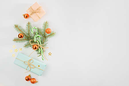 Christmas composition concept, gift boxes, spruce branches, Christmas balls toys on white background, copy space, top view Archivio Fotografico