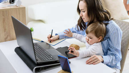 brunette woman with child sits at laptop making notes in notebook, online courses, remote work at home, Working from home concept