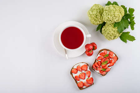 morning Breakfast concept, tea with hibiscus, sandwich with strawberries and cottage cheese, flowers on white background, still life, copy space, top view, tea party