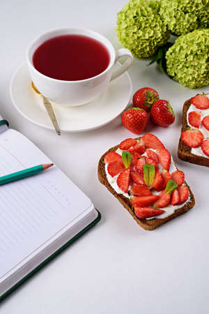 morning tea, still life, Notepad with pencil, tea with hibiscus, sandwich with strawberries and cottage cheese, flowers on white background, vertical Archivio Fotografico