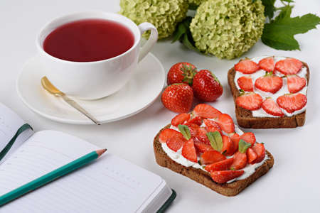 morning tea, still life, Notepad with pencil, tea with hibiscus, sandwich with strawberries and cottage cheese, flowers on white background,, planning your day concept Archivio Fotografico