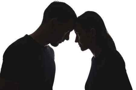 black and white silhouettes of portraits men and women on white background stand opposite each other, touching their foreheads. feminism, masculism concept