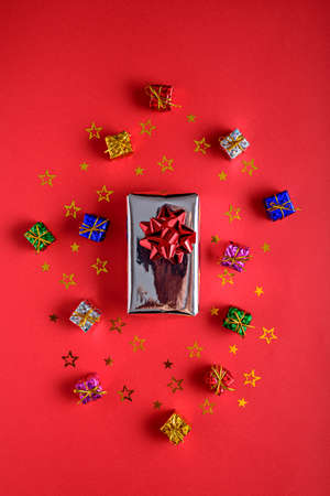 gift boxes with sequins stars on red background, top view, vertical