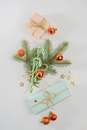 Christmas composition concept, gift boxes, spruce branches, Christmas balls toys, stars on white background, vertical, top view Archivio Fotografico