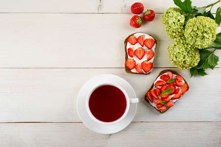 morning Breakfast concept, tea with hibiscus, sandwich with strawberries and cottage cheese, flowers on white wooden background, still life, copy space, top view