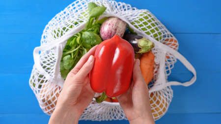 product delivery concept. Red pepper in hand, vegetables in eco bag on blue background, top view, healthy diet Archivio Fotografico