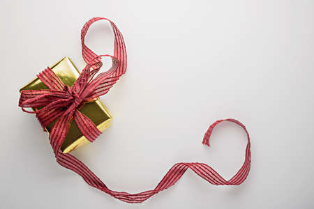 Golden gift box with Burgundy ribbon on white background, copy space, top view Archivio Fotografico