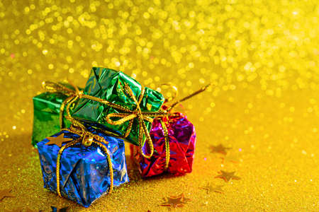 gift boxes on gold shiny background, copy space, christmas composition Archivio Fotografico