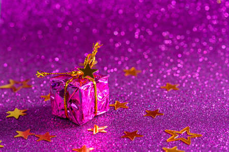 small gift box on purple shiny background, copy space, christmas composition,