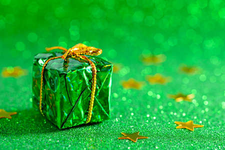 small gift box on green shiny background, copy space, christmas composition