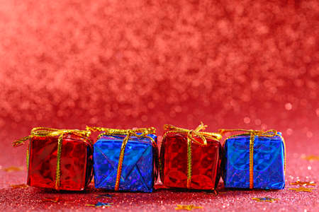 gift boxes in row on red shiny background, copy space, christmas composition, present surprise Archivio Fotografico