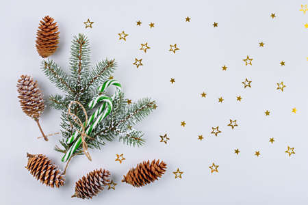 Christmas composition, fir-tree branches, cones, lollipops with sequins on white background, top view, copy space