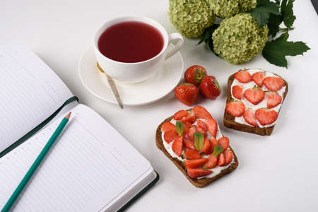 morning tea, still life, Notepad with pencil, flower, tea with hibiscus, sandwich with strawberries and cottage cheese, Feminine lifestyle composition, closeup