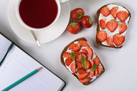 morning tea, still life, Notepad with pencil, tea with hibiscus, sandwich with strawberries and cottage cheese, Feminine lifestyle composition, top view Archivio Fotografico
