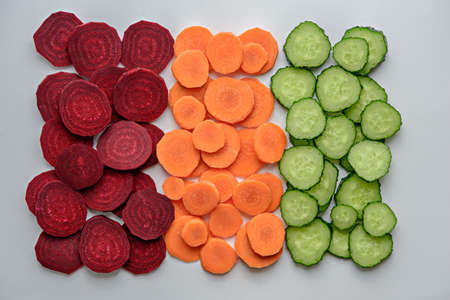 mix of vegetable slices beetroot, carrot, cucumber on white background, vegetable composition, top view Archivio Fotografico