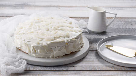 homemade coconut white cake on marble Board on white background, home cooking, wedding cake Archivio Fotografico