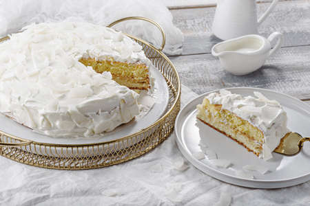 homemade coconut white cake on white background, portion of cake on plate with spatula, home cooking
