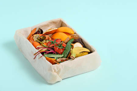 food trash, vegetable peels in compost bin on blue background, compost concept. Copy space, Sustainable and zero waste,
