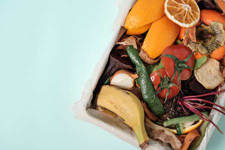 top view vegetable peels in compost bin on blue background, compost concept. Sustainable and zero waste, food leftovers Фото со стока