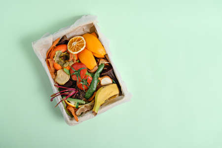 top view vegetable peels in compost bin on green background, compost concept. Copy space, Sustainable and zero waste, food leftovers Фото со стока